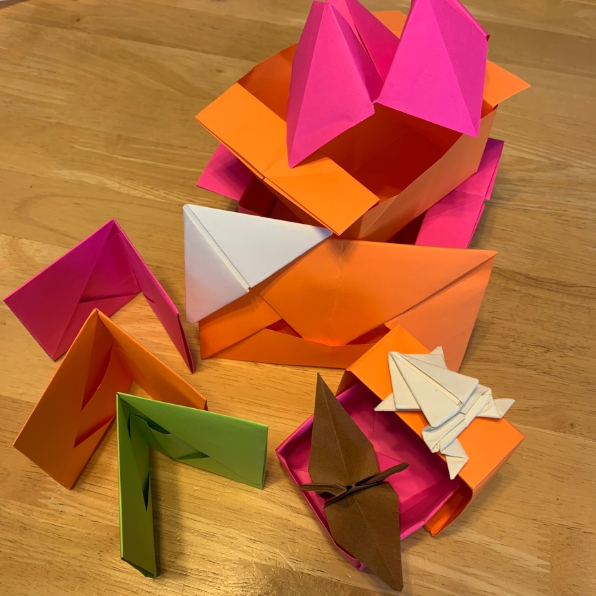 A collection of various origami models arranged together on a tabletop in bright orange, pink, and green. There are wallets standing in a row, boxes and envelopes, topped with a crane and a frog, a bookmark rests at the corner of an envelope, and a fortune teller props up from behind.
